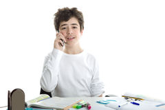 Caucasian smooth-skinned boy talking on cell phone on homeworks. Smiling handsome Caucasian smooth-skinned boy is talking on cell phone while doing homework and Royalty Free Stock Image