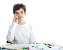 Caucasian smooth-skinned boy talking on cell phone on homeworks. Smiling handsome Caucasian smooth-skinned boy is talking on cell phone while doing homework and Stock Images