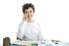 Caucasian smooth-skinned boy talking on cell phone on homeworks. Smiling handsome Caucasian smooth-skinned boy is talking on cell phone while doing homework and Stock Photo