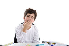 Caucasian smooth-skinned boy yawning on homeworks. Tired Caucasian smooth-skinned boy sits in front of homework wearing a white long sleeve t-shirt and yawns Stock Images