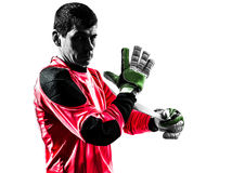 Caucasian soccer player goalkeeper man adjusting gloves silhouet. One caucasian soccer player goalkeeper man adjusting gloves in silhouette isolated white Royalty Free Stock Images