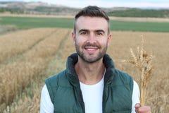 Caucasian sorridente felice trenta anni dell'agricoltore che sta fiero davanti ai suoi giacimenti di grano Fotografie Stock