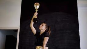 Caucasian sportbrunett som poserar i framdel av kameran med guld- koppar i hennes händer stock video