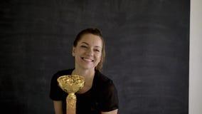 Caucasian sportbrunett som poserar i framdel av kameran med guld- koppar i hennes händer arkivfilmer