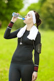 Caucasian Sportive Woman Drinking Water During Her Regular Joggo Stock Photography