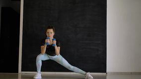 Sporty brunette poses for the camera with blue dumbbells in her hands stock video