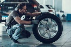 Caucasian stilig auto mekaniker Check Car Wheel royaltyfria foton