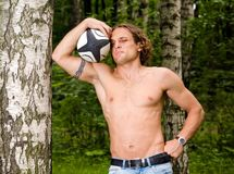 Caucasian strong man playing rugby ball outdoors. Caucasian strong man playing funny rugby ball outdoors Royalty Free Stock Image