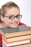 Caucasian student in eye glasses on pile of book Royalty Free Stock Photos