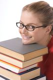Caucasian student in eye glasses on pile of book Stock Images