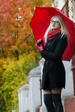 Caucasian student girl with red fully collapsible. Umbrella in hands and cat eye glasses is posing at autumn street background Royalty Free Stock Photography