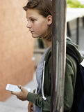 Caucasian student girl standing holding smart phone Stock Image