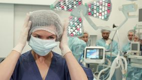 Surgical nurce puts on medical mask. Caucasian surgical nurse putting on medical mask before operation. Female medical worker in steril gloves standing against Royalty Free Stock Photography