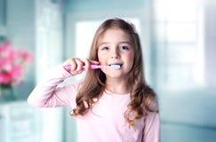 Caucasian tänder för barnflickalokalvård i badrum royaltyfria bilder