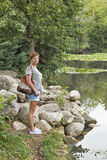 Caucasian tanned middle aged woman stands in front of lake Royalty Free Stock Photography