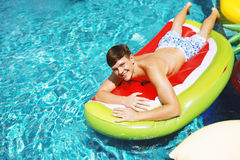 Caucasian tattooed man floating in the swimming pool by inflatab Royalty Free Stock Photos