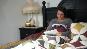 A Caucasian teacher grading papers in her bed at night - the class is failing stock video