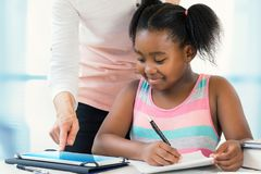 Caucasian teacher helping little black girl with schoolwork on t. Close up portrait of little african girl struggling with school work.Caucasian teacher showing Royalty Free Stock Photography