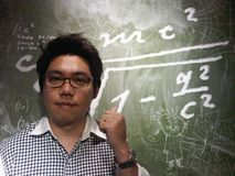 Caucasian teacher with his glasses use thump finger point to the blackboard. Portrait of caucasian teacher with his glasses use thump finger point to the Stock Photo