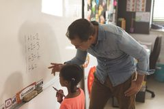 Caucasian teacher learning mathematics to a mixed-race school girl on a whiteboard royalty free stock image