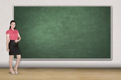 Caucasian teacher standing in the classroom. Picture of Caucasian female teacher looking at the camera while standing in the classroom Stock Photos