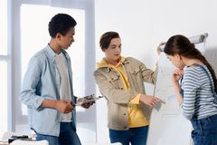 Caucasian teen boy presenting something on flipchart to multicultural teenagers. At home royalty free stock images