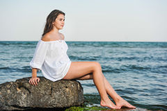 Caucasian teen girl in bikini and white shirt lounging on lava rocks by the ocean Royalty Free Stock Photo