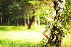 Caucasian teen girl with dark hair is standing near a tree with sad or dreamy face. Looking away. Royalty Free Stock Image