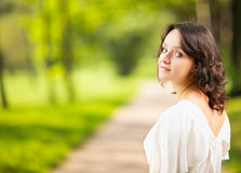 Caucasian teen girl with dark hair is walking away in park. She has turned back and is looking at camera. Stock Images