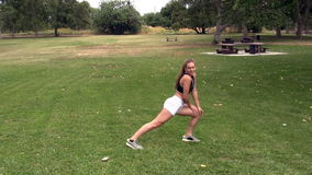 Caucasian teen girl stretching in white shorts black top at park stock video footage