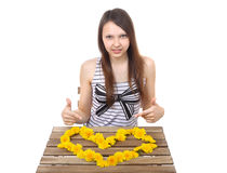 Caucasian teen girl, 15 years old, shows a yellow. Caucasian teen girl, brunette, 15 years old, shows a yellow valentine made from dandelion flowers on the Royalty Free Stock Photography