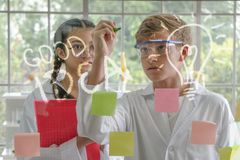 Caucasian teenage boy and Asian teenage girl as researchers writing mathematics formulas. And signs on glass board royalty free stock photo