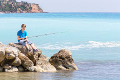 Caucasian teenage boy fishing with rod near sea and beach Stock Images