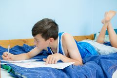 Teen boy doing homework on his bed stock images