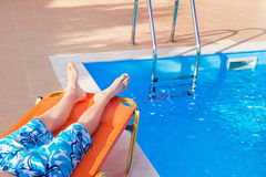 Caucasian teenage boy lying on stretcher near swimming pool Stock Image