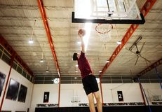 Caucasian teenage boy playing basketball alone on the court Royalty Free Stock Photography