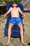 Teenage boy sunbathing in the garden. Caucasian teenage boy sunbathing in a garden wearing sunglasses Stock Photo