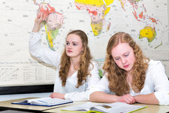 Caucasian teenage girl with learn finger in geography lesson. European teenage girl with learn finger in geography lesson. She sits side by side with her sister Royalty Free Stock Images