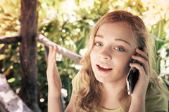 Caucasian teenage girl in a park talking on a cell phone Stock Images