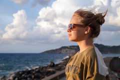 Caucasian teenage girl relaxing on a seacoast Stock Photos