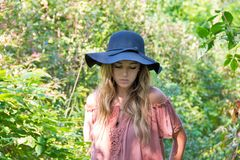 Caucasian teenage girl in summer woods. Caucasian teenage girl in sunlit summer woods with serious expression wearing black hat and off the shoulder blouse royalty free stock photography