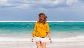 Caucasian teenage girl walking on the ocean coast Royalty Free Stock Photo