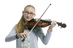 Caucasian teenage girl wears glasses and plays the violin royalty free stock photography