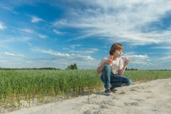 Caucasian teenager blowing soap bubble wand for making soap bubbles on dirt oat field road Stock Images