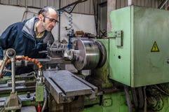 Caucasian tekniker som håller ögonen på headstocken av den vändande drejbänkmaskinen i fabrik arkivfoto