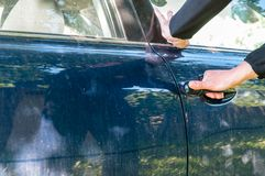 Caucasian thief hand trying to open a car door stock photography