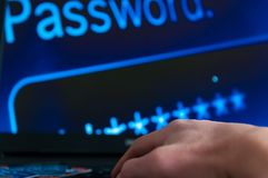 Caucasian thief hands on laptop keyboard with a bunch of stolen credit cards. royalty free stock photography