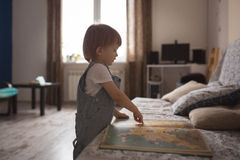 Caucasian Toddler boy playing with  book,  lifestyle. Caucasian Toddler boy playing with a book,  lifestyle, real interior toning Royalty Free Stock Photos
