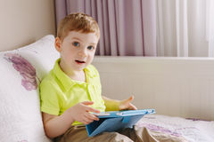 Caucasian toddler boy sitting in bed playing with digital tablet with funny face expression. Portrait of cute adorable white Caucasian toddler boy sitting in bed royalty free stock photo