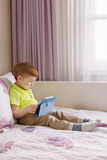 Caucasian toddler boy sitting in bed playing with digital tablet with funny face expression. Portrait of cute adorable white Caucasian toddler boy sitting in bed stock images